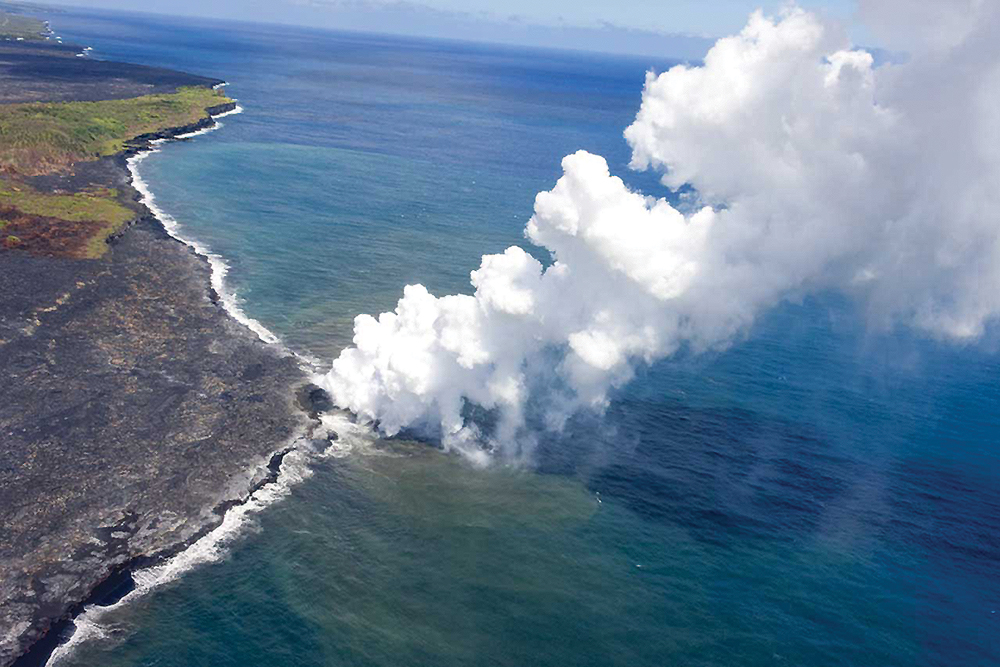 Vog plume where lava flows into the ocean